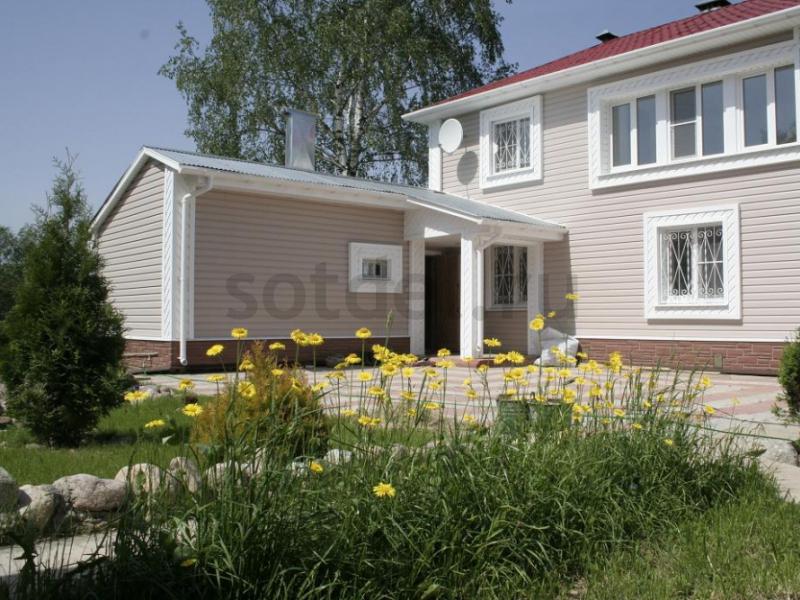 Фасад дома в цвете Sandalwood, уникальное оформление окон